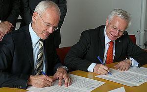 Ohm-Präsident Prof. Dr. Michael Braun und und FAU-Präsident Prof. Dr. Karl-Dieter Grüske unterzeichnen die Kooperationsvereinbarung. Foto: TH Nürnberg