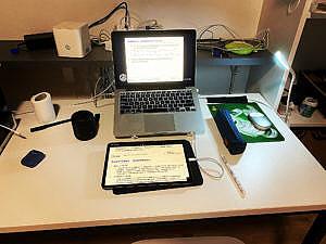 Schreibtisch mit Ipad und Laptop mit Studienunterlagen